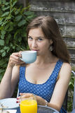 Ung kvinna som utomhus dricker te Arkivbild