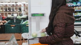 Ung kvinna som väger frukter med elektrisk våg i supermarket stock video