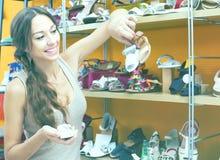 Ung kvinna som väljer barnskor Royaltyfria Bilder