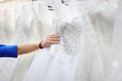 Ung kvinna som väljer den perfekta brud- klänningen under brud- shopping Royaltyfri Fotografi