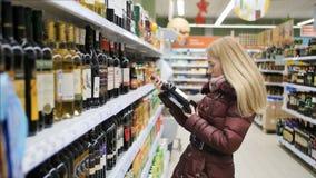 Ung kvinna som väljer en flaska av rött vin stock video