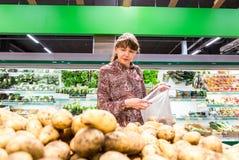 Ung kvinna som väljer nya potatisar Arkivbild