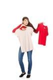 Ung kvinna som väljer skjortan Royaltyfri Foto