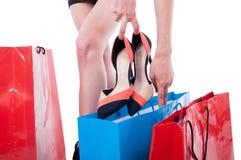 Ung kvinna som väljer skor i ett skolager royaltyfria bilder
