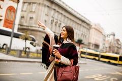Ung kvinna som välkomnar en taxi på gatan i staden Arkivfoto