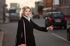 Ung kvinna som välkomnar en taxitaxi Royaltyfria Bilder