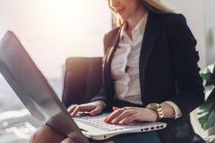 Ung kvinna som väntar i ett korridorsammanträde i det moderna kontoret som arbetar på bärbara datorn som talar på telefonen arkivfoto