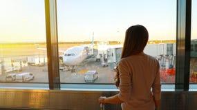 Ung kvinna som väntar i flygplats hennes flyg royaltyfri fotografi