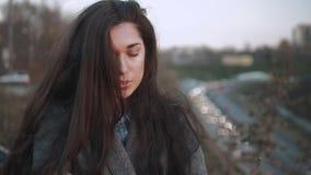 Ung kvinna som värme sig i höst Kall nedgångdag Kvinnafrysning på solnedgång på gatan med stadsbakgrund lager videofilmer