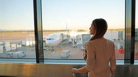 Ung kvinna som v?ntar i flygplats hennes flyg royaltyfri bild
