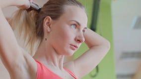 Ung kvinna som vilar efter genomkörare på idrottshallen Konditionkvinnlig som tar avbrottet efter utbildningsperiod i vård- klubb arkivfilmer