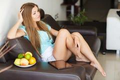 Ung kvinna som vilar hemmastatt sammanträde på en lädersvartsoffa Royaltyfria Foton