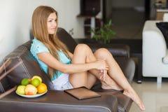 Ung kvinna som vilar hemmastatt sammanträde på en lädersvartsoffa Arkivfoto