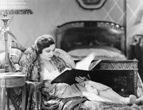 Ung kvinna som vilar i en fåtölj och en läsning en bok i hennes sängrum (alla visade personer inte är längre uppehälle och inget  royaltyfri fotografi