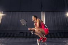 Ung kvinna som vilar, når att ha spelat badminton på idrottshallen royaltyfri fotografi