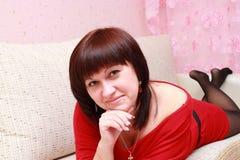 Ung kvinna som vilar på en sofa Fotografering för Bildbyråer