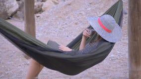 Ung kvinna som vilar på hängmattan arkivfilmer