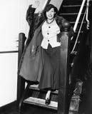 Ung kvinna som vinkar på en trappuppgång, och le (alla visade personer inte är längre uppehälle, och inget gods finns Leverantörw Royaltyfria Foton