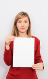 Ung kvinna som visar ett tomt ark av papper Royaltyfri Foto