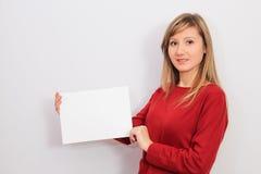Ung kvinna som visar ett tomt ark av papper Arkivbild