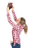 Ung kvinna som visar hennes tomma plånbok. fotografering för bildbyråer