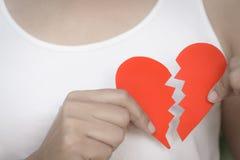 Ung kvinna som visar röd riven sönder pappers- hjärta Fotografering för Bildbyråer