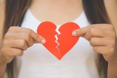 Ung kvinna som visar röd riven sönder pappers- hjärta Royaltyfri Bild