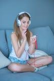 Ung kvinna som väljer musik på hennes spelare MP3 Arkivfoton