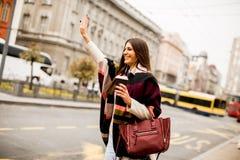Ung kvinna som välkomnar en taxi på gatan i staden Royaltyfri Bild