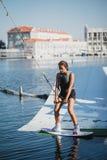 Ung kvinna som wakeboarding på havet Arkivfoton