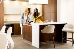 Ung kvinna tre i köket Arkivbilder