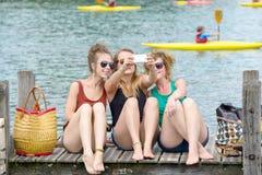 Ung kvinna tre på stranden med deras telefon royaltyfri bild