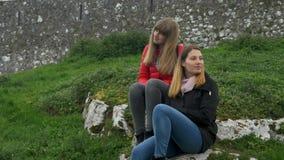 Ung kvinna två att koppla av i det gröna landskapet av Irland arkivfilmer
