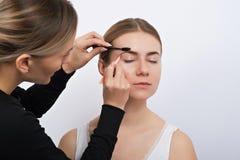Ung kvinna under ett ögonbrynkorrigeringstillvägagångssätt Fotografering för Bildbyråer