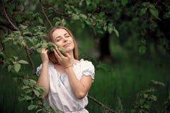 Ung kvinna upp på äpplen för en stegeplockning från ett äppleträd på royaltyfri fotografi