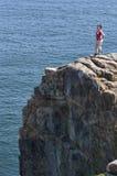 Ung kvinna upptill av en klippa som förbiser havet Arkivbild
