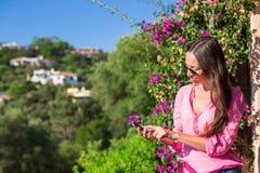 Ung kvinna utomhus och se telefonen Fotografering för Bildbyråer