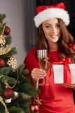 Ung kvinna vid en christmastree Fotografering för Bildbyråer