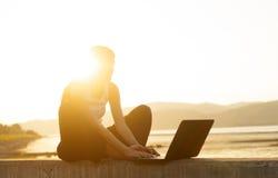 Ung kvinna vid floden i susnset med bärbara datorn Royaltyfri Bild