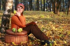 Ung kvinnaavläsningsbok i fallpark Royaltyfri Fotografi