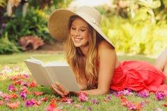 Ung kvinnaavläsningsbok utanför Arkivfoto