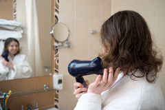 Ung kvinnadrying henne hår Royaltyfri Foto