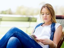 Ung kvinnaläsning som en boka parkerar in royaltyfria foton