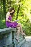 Ung kvinnaläsning som en boka parkerar in royaltyfri fotografi