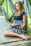 Ung kvinnaläsning bokar Royaltyfri Bild
