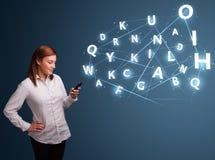Ung kvinnamaskinskrivning på smartphone med kick - tech 3d märker commi Arkivfoto