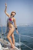 Ung kvinnasegling på yachten Fotografering för Bildbyråer