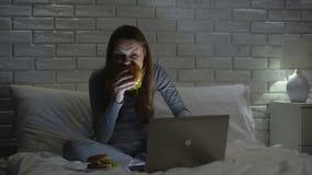 Ung kvinnlig ätahamburgare, medan surfa rengöringsduk på natten på säng, skräpmat arkivfilmer