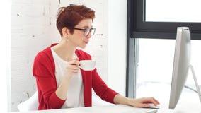 Ung kvinnlig aff?rsman med kaffekoppen p? tabellen i modernt kontor lager videofilmer
