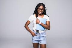 Ung kvinnlig afrikansk amerikanh?gskolestudent i exponeringsglas som rymmer b?cker isolerade p? vit arkivfoto